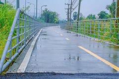 在雨以后的湿路划分的黄线成两条车道 库存图片