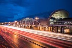 在雨以后的蓝色小时与轻的足迹的交通在火车站旁边 库存照片