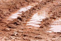 在雨以后转动在路、水坑和泥的踪影 在拖拉机,挖掘机,汽车,在泥泞的足迹的汽车轮胎轨道土壤的踪影  库存照片