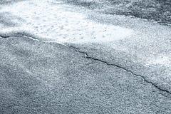 在雨天期间,街道路 与雨珠的水水坑 免版税库存图片