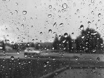 在雨天浇灌在车窗的下落 免版税库存照片