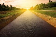 在雨季的日出和灌溉运河 免版税库存照片