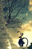 在雨水坑的反射自行车在人造偏光板 库存图片