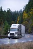 在雨秋天弯曲道路的现代半卡车拖车 库存照片