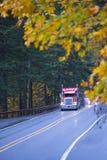 在雨秋天森林高速公路的红色大半船具卡车 免版税库存照片