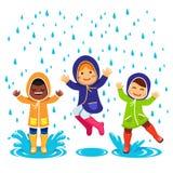 在雨衣和胶靴使用的孩子 免版税库存图片