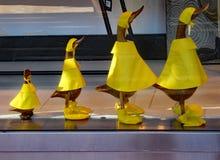 在雨衣的鸭子小雕象在显示 图库摄影