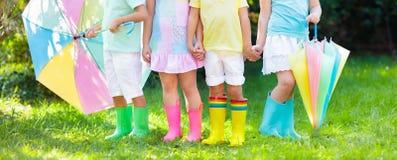 在雨靴的孩子 启动橡胶的子项 库存照片