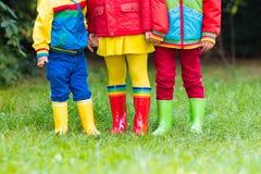 在雨靴的孩子 启动橡胶的子项 免版税库存图片