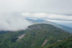 在雨,与灰色天空的绿色风景前的山 免版税库存照片