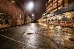 在雨以后涂柏油街道路在夜城市 与街道画的停车场在砖墙上 库存图片