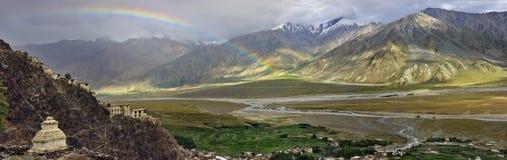 在雨以后的巨大的高山谷,大弧是明亮的彩虹通过峡谷,前景的白色Buddhis 库存照片