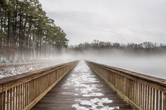 在雪、冰和雾的钱的湖边钓鱼码头 免版税库存照片