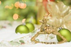 在雪、电灯泡和丝带中的金黄圣诞节驯鹿装饰品 库存照片