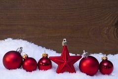 在雪、红色球和一个星的木圣诞节背景 免版税库存照片