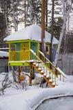 在雪下的五颜六色的树上小屋 免版税库存照片