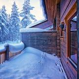 在雪下的大阳台在森林村庄 免版税库存照片