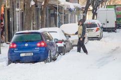 在雪下的汽车在街道上在冬天波摩莱,保加利亚 免版税库存照片