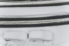 在雪下的汽车在街道的一个停车场在冬天降雪期间 库存照片