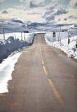 在雪中的路在漂移挪威山 库存图片