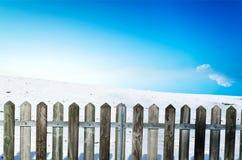 在雪倾斜的木篱芭 库存图片