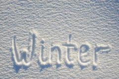 在雪写的冬天文本为纹理或背景-寒假概念 晴天,与阴影的明亮的光,平的位置, 免版税库存图片