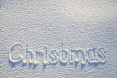 在雪写的圣诞节文本为纹理或背景-寒假概念 晴天,与阴影的明亮的光,平的位置, 库存图片