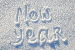 在雪写的新年文本为纹理或背景-寒假概念 晴天,与阴影的明亮的光,平的位置, 免版税库存图片