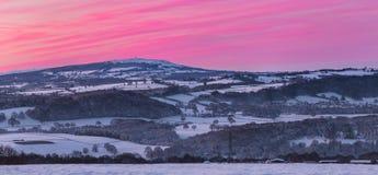 在雪和五颜六色的日出天空盖的风景小山 免版税库存照片