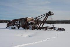 在雪和冰埋置的铜挖泥机 库存照片