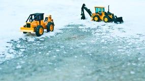 在雪和冰川覆盖的路的两辆铲车 免版税库存照片