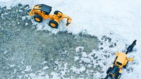 在雪和冰川覆盖的路的两辆铲车 图库摄影