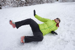 在雪和冰滑倒的妇女 免版税库存图片