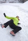 在雪和冰滑倒的妇女 免版税库存照片