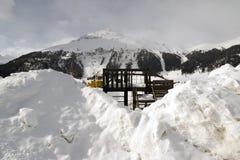 在雪和多雪的山下的一个孩子操场和一个小镇在阿尔卑斯瑞士 库存图片