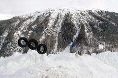 在雪和多雪的山下的一个孩子操场和一个小镇在阿尔卑斯瑞士 免版税库存照片