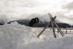 在雪和多雪的山下的一个孩子操场和一个小镇在阿尔卑斯瑞士 免版税库存图片