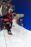 在雪和岩石的上升的队 免版税库存照片