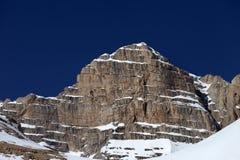在雪和蓝色清楚的天空的岩石 库存图片