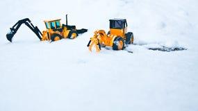 在雪埋没的两玩具forklays 图库摄影