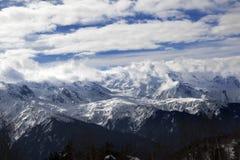 在雪山和阳光多云天空的看法冬天晚上 免版税库存图片