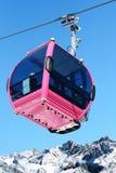 在雪山峰的桃红色缆车客舱 图库摄影