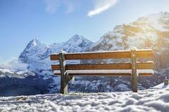 在雪山阿尔卑斯日出的美好的长木凳就座与 免版税库存图片