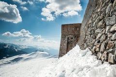 在雪山顶部的老石墙堡垒城堡 图库摄影
