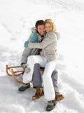 在雪撬的新夫妇 库存图片