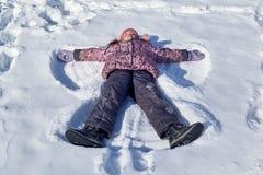 在雪是天使的姿势的一个孩子 免版税库存照片