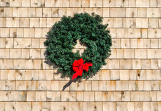 在雪松木瓦墙壁上的圣诞节花圈 库存照片