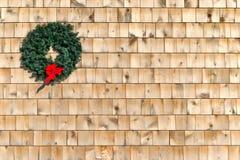 在雪松木瓦墙壁上的小圣诞节花圈 免版税库存图片
