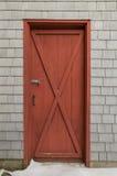 在雪松的红色谷仓样式门震动木瓦背景 库存照片