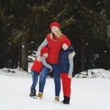 在雪森林里照顾和她的两个儿子获得乐趣在冬天 图库摄影